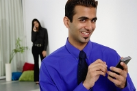 Businessman using PDA, smiling at camera, woman in the background - Asia Images Group