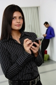 Businesswoman with PDA, looking at camera - Asia Images Group