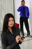 Businesswoman with PDA, looking up at camera, man in the background, using mobile phone - Asia Images Group