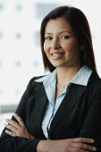 Businesswoman smiling at camera, arms crossed - Asia Images Group