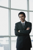 Young businessman arms crossed, looking at camera - Asia Images Group