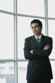 Young businessman arms crossed, standing by window - Asia Images Group