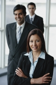 Businesswoman smiling at camera, businessmen behind her - Asia Images Group
