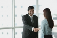 Businessman and businesswoman shaking hands - Asia Images Group