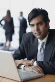 Businessman sitting in front of laptop, looking at camera - Asia Images Group