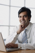 Businessman sitting in front of laptop, hand on chin, looking at camera - Asia Images Group