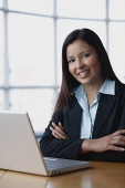 Businesswoman sitting in front of laptop, arms crossed, smiling - Asia Images Group