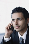 Young businessman with mobile phone, head shot - Asia Images Group