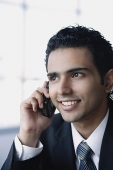 Young businessman on the phone, smiling, head shot - Asia Images Group