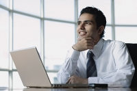 Young businessman sitting in front of laptop, smiling, looking away - Asia Images Group