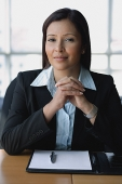 Businesswoman looking at camera, hands clasped - Asia Images Group