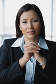 Businesswoman looking at camera, hands clasped, portrait - Asia Images Group