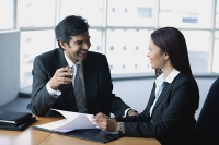 Businessman and businesswoman in office, having a discussion - Asia Images Group