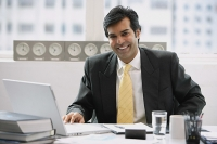 Businessman sitting in office, smiling at camera - Asia Images Group