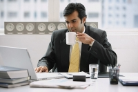 Businessman in office using laptop, drinking from cup - Asia Images Group