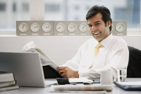 Businessman sitting in office, holding newspaper, smiling - Asia Images Group