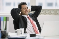 Businessman sitting in office, hands behind head, smiling - Asia Images Group