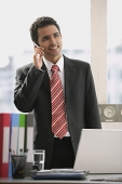 Businessman standing in office, using mobile phone - Asia Images Group