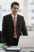 Businessman standing in office, looking at camera - Asia Images Group