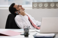 Businessman in office, using mobile phone - Asia Images Group