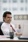 Businessman in office, holding coffee mug, smiling - Asia Images Group