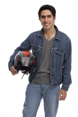 Man carrying motorcycle helmet, looking at camera - Asia Images Group