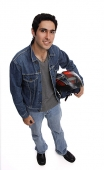 Man carrying motorcycle helmet, looking up at camera - Asia Images Group