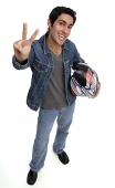 Man carrying motorcycle helmet, looking up at camera, making hand sign - Asia Images Group