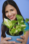 Woman holding potted plant, focus on the background - Asia Images Group