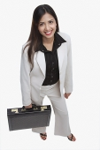 Businesswoman looking at camera, carrying briefcase - Asia Images Group