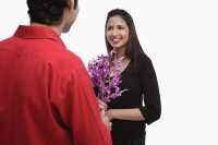 Woman holding flowers, smiling at man in front of her - Asia Images Group