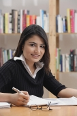 Woman studying in library, looking at camera - Asia Images Group