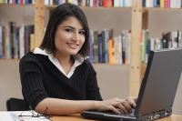 Woman in library, using laptop, looking at camera - Asia Images Group