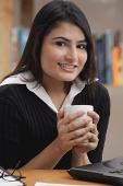 Woman holding a cup, smiling at camera - Asia Images Group