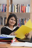 Woman in library, holding yellow folder - Asia Images Group