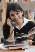 Woman in library, using telephone, looking at camera - Asia Images Group
