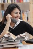 Woman in library, using telephone - Asia Images Group