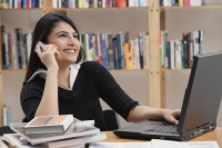 Woman in library, using mobile phone - Asia Images Group
