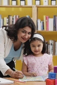 Woman teaching young girl, both smiling at camera - Asia Images Group