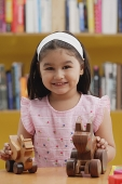 Young girl with wooden toys, smiling at camera - Asia Images Group