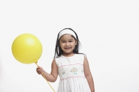 Young girl in white dress, holding a yellow balloon - Asia Images Group