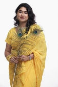 Woman in yellow sari holding peacock feather - Asia Images Group