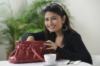 Woman in cafe, looking in bag - Asia Images Group