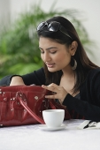 Woman in cafe, looking into her bag - Asia Images Group
