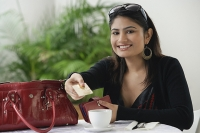 Woman in cafe, holding credit card toward camera - Asia Images Group