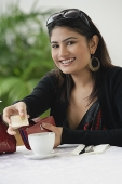 Woman in cafe, paying with credit card - Asia Images Group