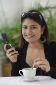 Woman in cafe, using mobile phone - Asia Images Group