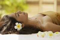 A woman lying down with frangipani flowers around her - Asia Images Group