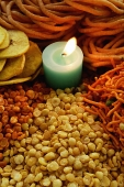A mixed snack platter with a candle - Asia Images Group