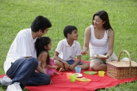 A family have a picnic together in the park - Asia Images Group